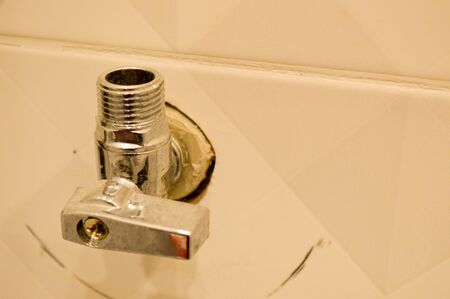 Metallic iron shiny chrome plumbing fittings with thread and valve in the wall of ceramic tiles. Imagens