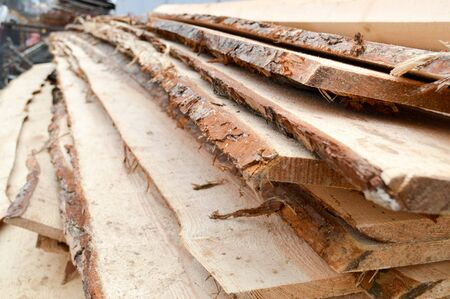 Lots of long wooden natural planed boards and sticks at a sawmill. The background. Texture. Concept: timber harvesting for the wood industry.