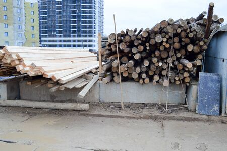 A lot of long wooden natural planed logs and boards at a sawmill. The background. Texture. Concept: timber harvesting for the wood industry.