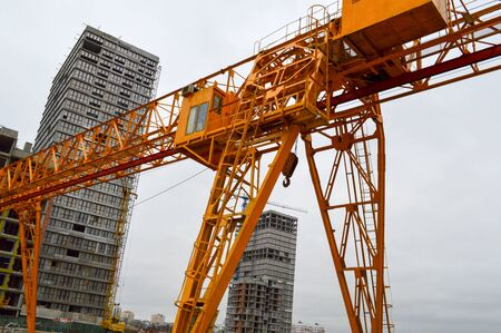 A large modern construction site in the construction of buildings and houses with appliances and many large high tower and stationary industrial powerful cranes and building materials.