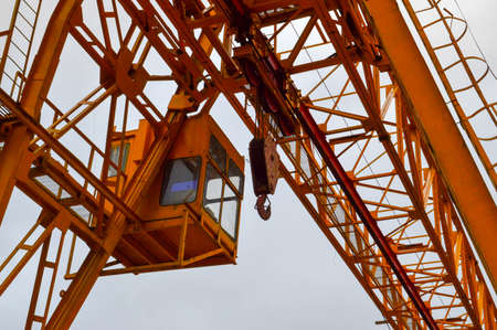 High heavy yellow metal iron load-bearing construction stationary industrial powerful gantry crane of bridge type on supports for lifting cargo on a modern construction site of buildings and houses.