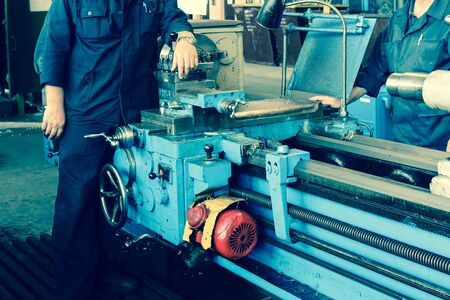 Large metal iron industrial turning and screw cutting machine for processing metal and parts with spare parts and a worker in a robe at the factory.