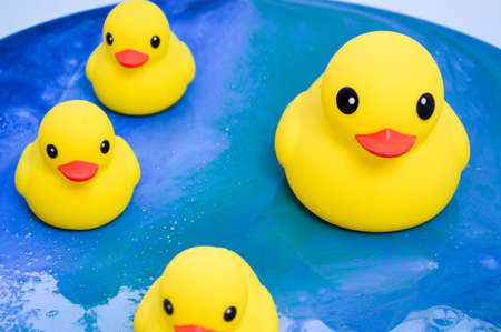 yellow rubber ducks floating on the ocean surface of epoxy. decorative toys stand on a glossy interior picture in the form of water with sun glare. abstract background.