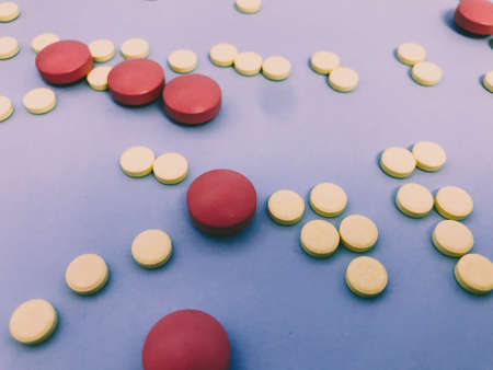 bright pink and yellow pills of volumetric and round shape on a blue matte and paper background. medicines to preserve and enhance human health. medical background. Stockfoto