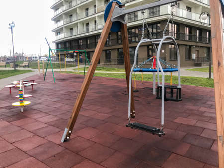 swing for small children in the courtyard of the residential complex. high chair for rocking the baby. active rest with children. a black swing for sitting a child and a parent who rolls it.