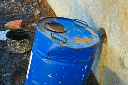 a bright blue barrel stands on the road. a flammable liquid is poured inside the barrel. a barrel with a hole inside stands in the center of the city at a construction site.