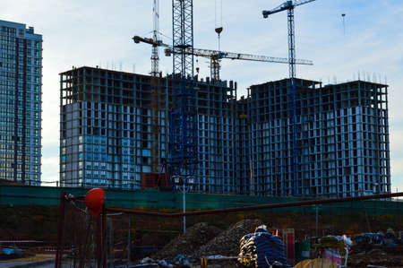 tall concrete houses are being built in the city center. multi-storey buildings, concrete boxes against the backdrop of large cranes for carrying heavy loads. helmet, a builder's uniform, hang nearby.