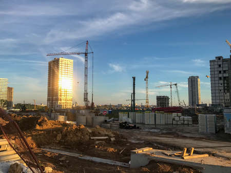 construction cranes are erecting new houses from blocks. new constructions, places of life of people. in houses panoramic glazing, where the sunset sun is reflected.
