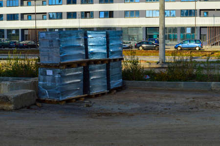 the construction site is packed with material for the construction of new houses in the city. building material in a transparent thick film, on wooden pallets, stands on sandy ground. Stock fotó