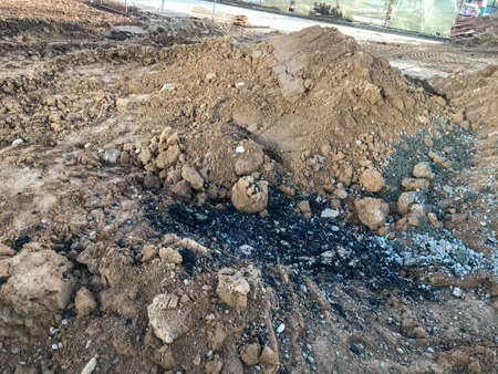 a pile of sand piled up at a construction site. black and viscous fuel oil is poured onto the ground. building materials for the construction of new houses. stones and debris in the sand.