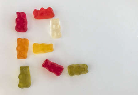 The letter R made from beautiful sweet delicious multi-colored chewy juicy fruit gummy candies of bears on a white background. Sweet alphabet.