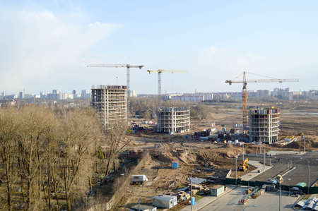 Top view of a large construction site with cranes and buildings houses concrete monolithic frame panel multi-storey skyscrapers of the big city of the metropolis.