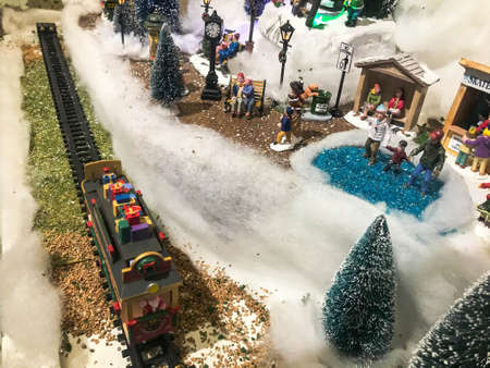 New Year's landscape. toy miniature for the showcase. cute showcase, hand made composition. there is a train in the center, the carriages are covered with snow.