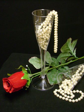 champagne glasses full of pearls and a single red velvet rose on a black background for valentines day