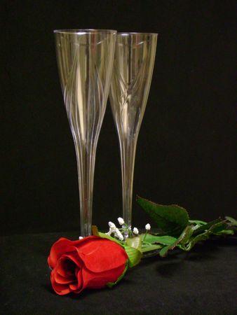 2 champagne glasses 1 single red velvet rose on black background romantic Stok Fotoğraf
