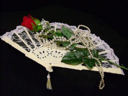 still llife single red velvet rose antique fan and pearls