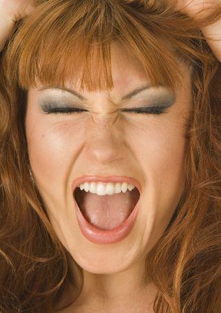 A beautiful redheaded woman screams in stress Stock Photo