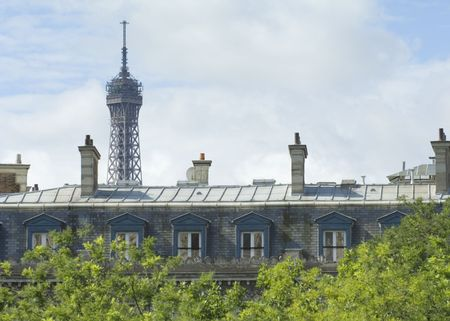 The top of the Eiffel Tower climbing above the parisian rooftops in Paris, France