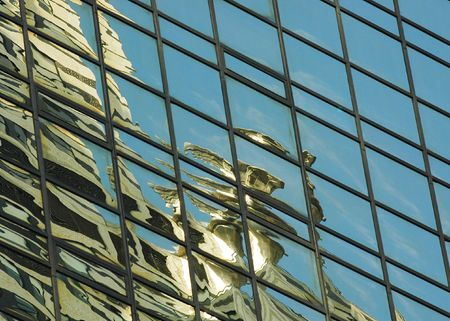 A reflection of an Art Deco gargoyle on the Chrysler Building, reflected in the glas of a skyscraper in Manhattan, New York Stock Photo