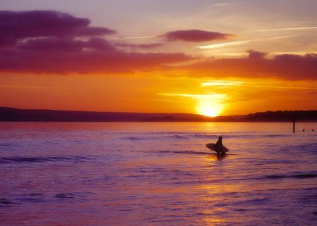 A surfer calls it a day and heads for the beach at sunset in Bournemouth, England