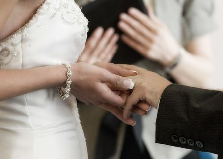 Bride and Groom exchange wedding rings at their wedding Stock Photo