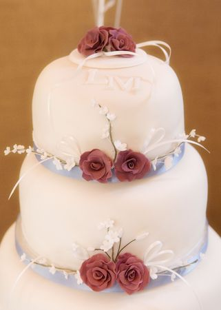 Beautiful wedding cake and red roses made of icing