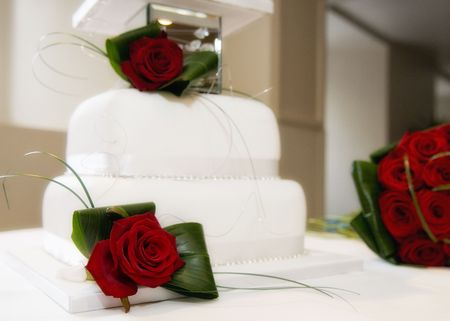 Beautiful wedding cake and red roses