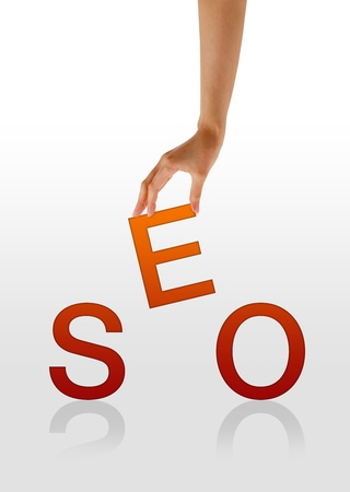 keywords link: High resolution graphic of a hand holding the letter E from the word SEO. Stock Photo