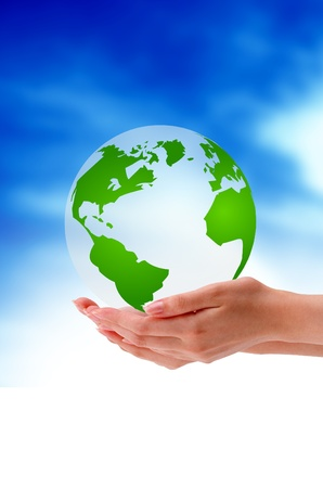 Hand holding a globe on cloud background.