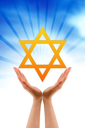 Hand holding a Jewish Star on cloud background.