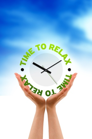 relieve: Hand holding a relax clock sign on cloud background. Stock Photo