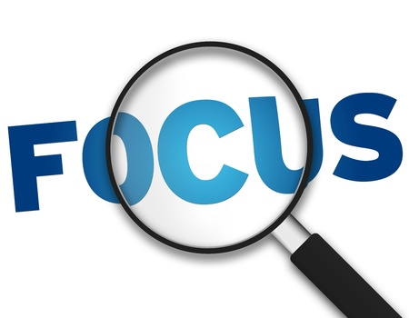 focus on the goal: Magnifying Glass with the word Focus on white background.
