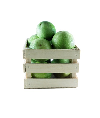 Green pomegranates in a wood box on white background.