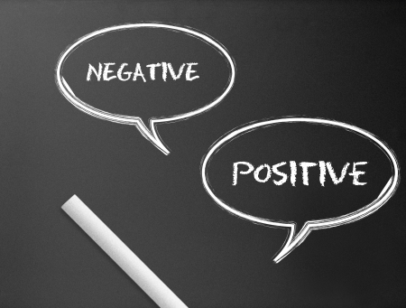 POSITIVE NEGATIVE: Dark chalkboard with a negative, positive speech bubbles illustration.
