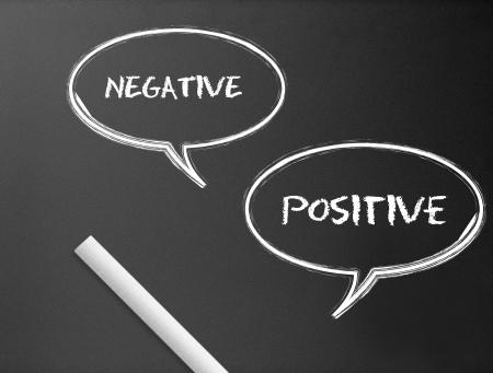 Dark chalkboard with a negative, positive speech bubbles illustration.