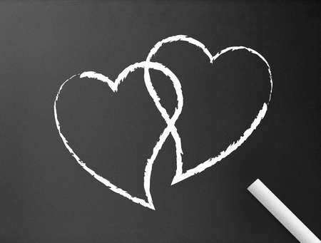Dark chalkboard background with two hearts illustration.  Stock fotó