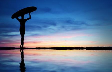 Surfař chodit na pláž do západu slunce.