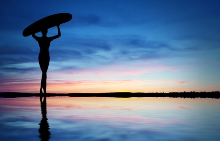 surfer: Surfer walking on the beach into the sunset. Stock Photo