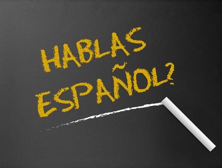language school: Dark chalkboard with a question. Hablas Espanol?