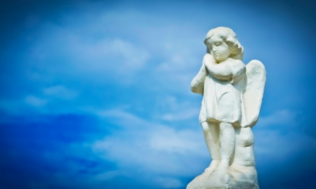 Praying sculpture angel on cloud background. photo