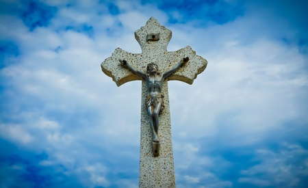 Religious Cross sculpture on blue cloud background. Stock Photo - 11983578