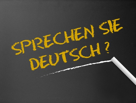 university word: Dark chalkboard with a question: Sprechen Sie Deutsch?  Stock Photo