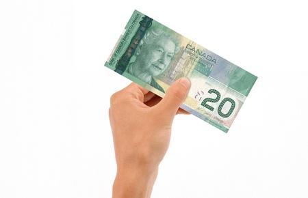 Une main tenant un billet de 20 dollars canadiens islolated sur fond blanc.