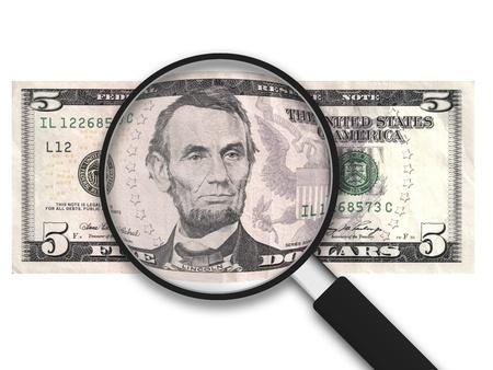letra de cambio: Lupa con 5 dólares estadounidenses Nota sobre fondo blanco Foto de archivo