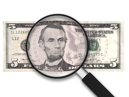letra de cambio: Lupa con 5 d�lares estadounidenses Nota sobre fondo blanco Foto de archivo