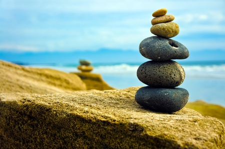 rock pile: Zen Stone stacked together on blue coud background.  Stock Photo
