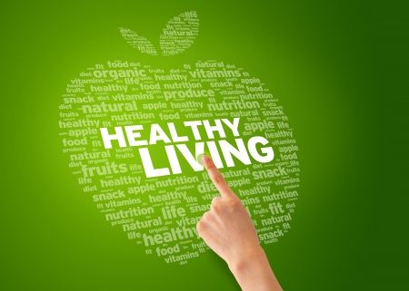 living: Finger pointing at an Healthy Living Apple on green background.