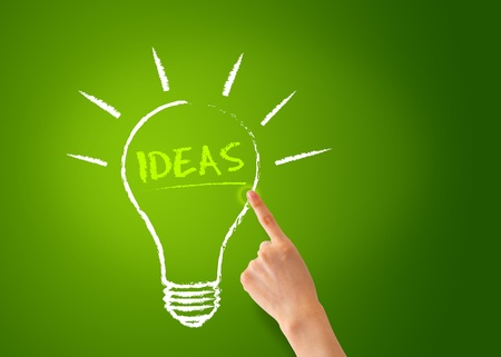 A Hand pointing of a Ideas Lightbulb on green background.
