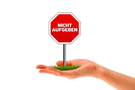 injunction: Hand holding stop sign with the words Nicht Aufgeben