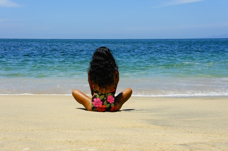 Latin Woman relaxing at a tropical beach photo